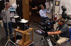 A single HD camera with teleprompter, a light panel, a floor director. some lights, and an SD field monitor.