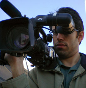 David S Waxman stands with a shoulder-mount Pro HD camcorder